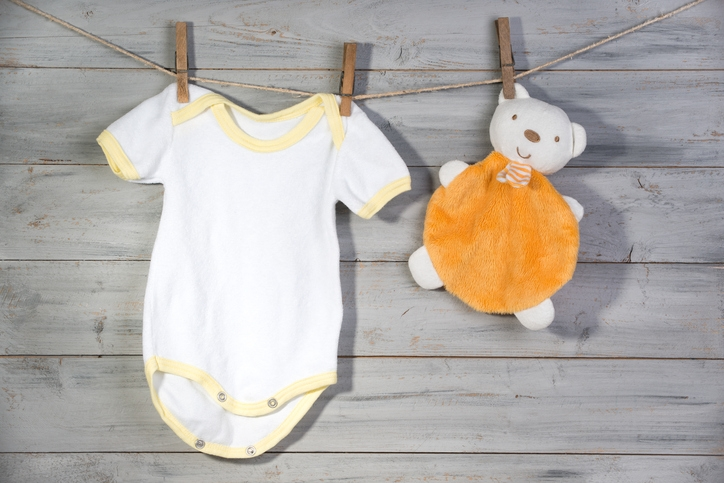 Baby clothes and bear toy on a clothesline