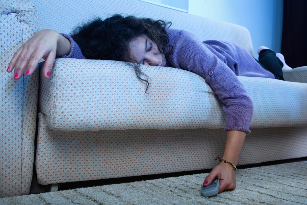 Young woman sleep on the couch in a dark living room with the TV on amd remote in hand.