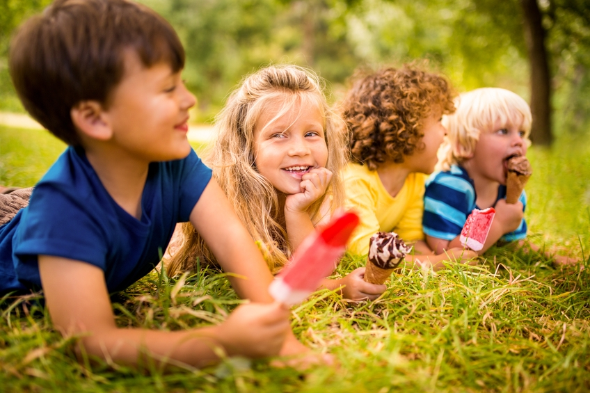 Friendly kids happily enjoying ice creams in the park