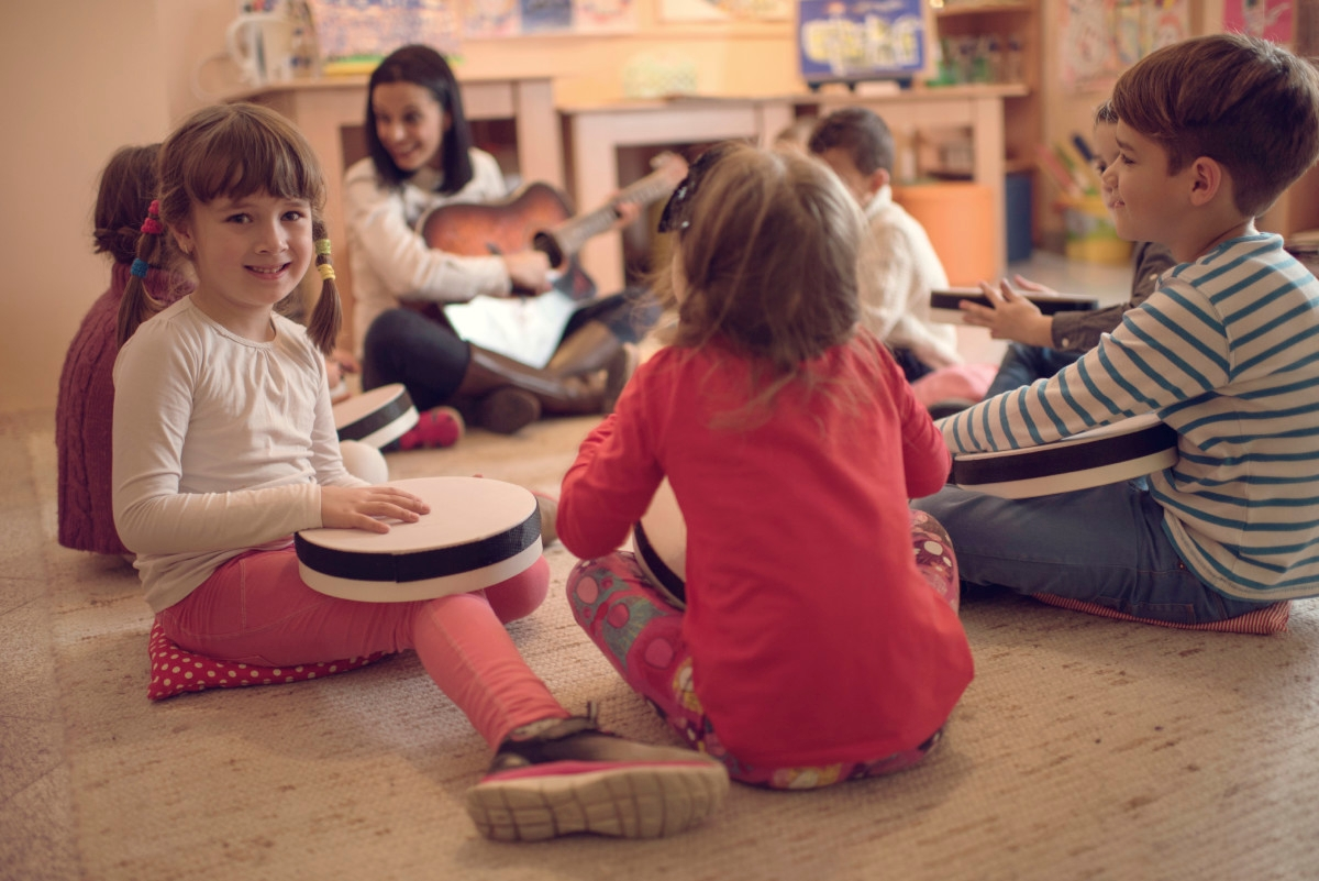 Happy little girl having a music class with her friends and teacher in a preschool and looking at the camera.
