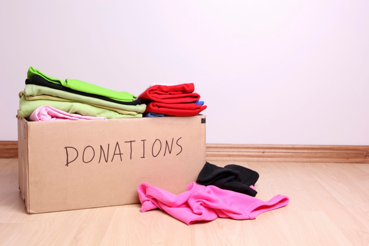 Box with clothes for donations on a laminate floor