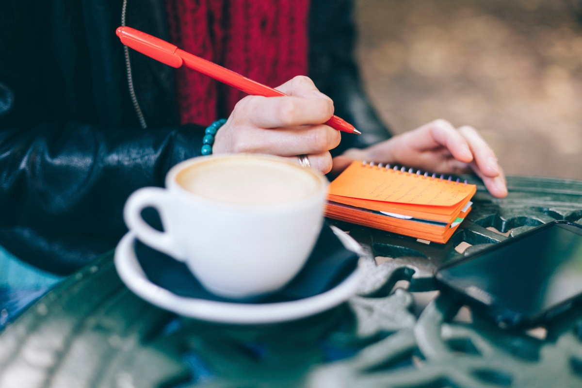 Woman in a cafe writing in notebook