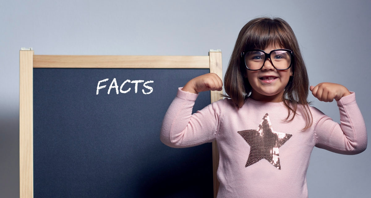 portrait of funny nerd girl with eyeglasses posing and stretching muscles.posing with behind blackboard with facts word on it.