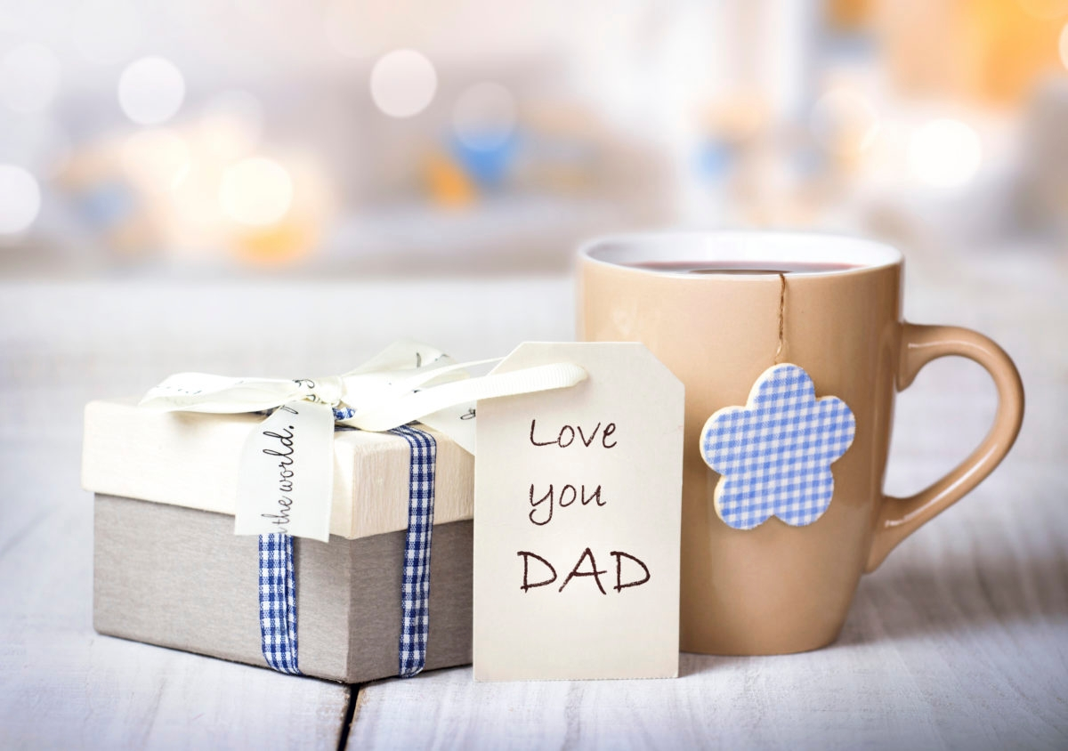 Father's day holiday greeting card.Mug tea coffee and present gift box tag on wooden table blur lights background empty space.Love you dad message.