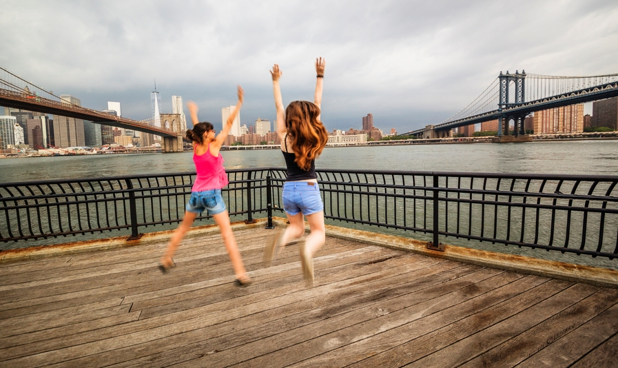 Two girls, sisters, jumping at the waterfront