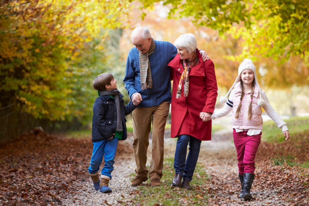 Grandparents With Grandchildren Walking Along Autumn Path Embracing Holding Hands Outdoors Caption