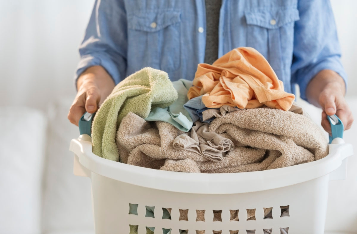 Midsection of mature man holding laundry basket at home