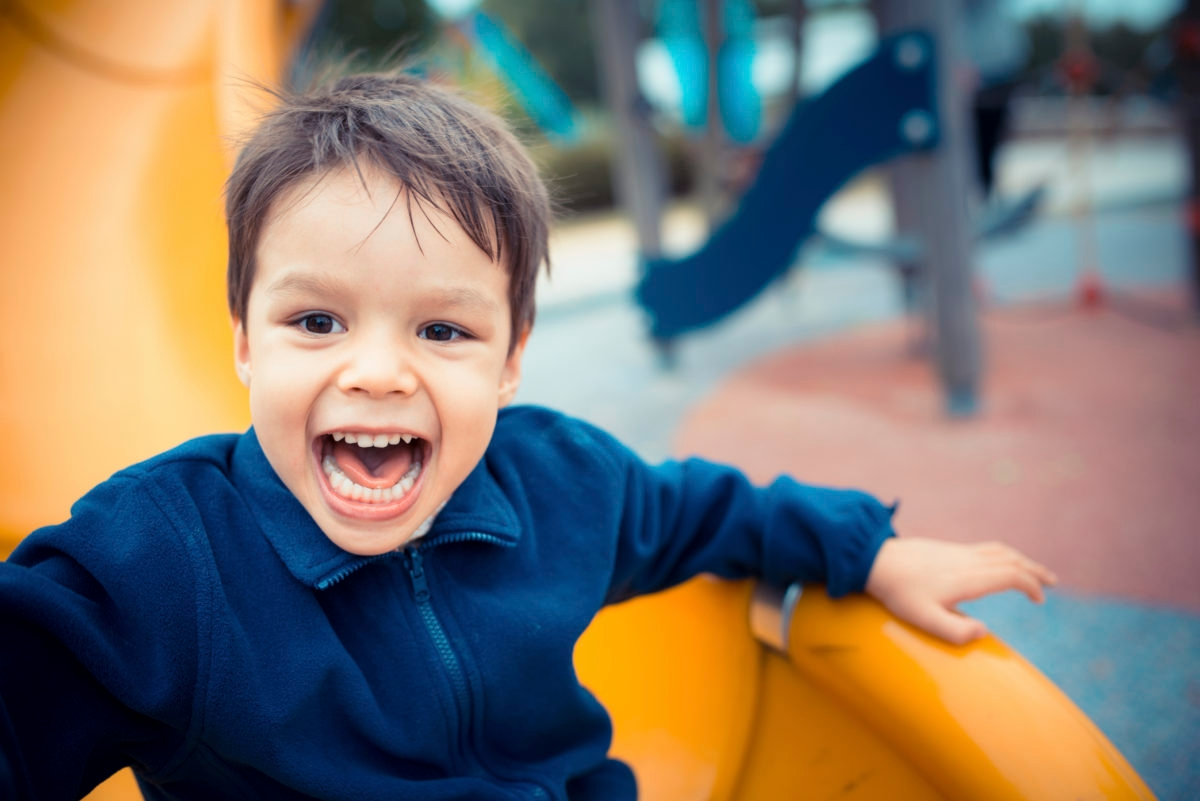 A cute young mixed race Asian Caucasian boy plays happily on a yellow slide in an outdoor playground.