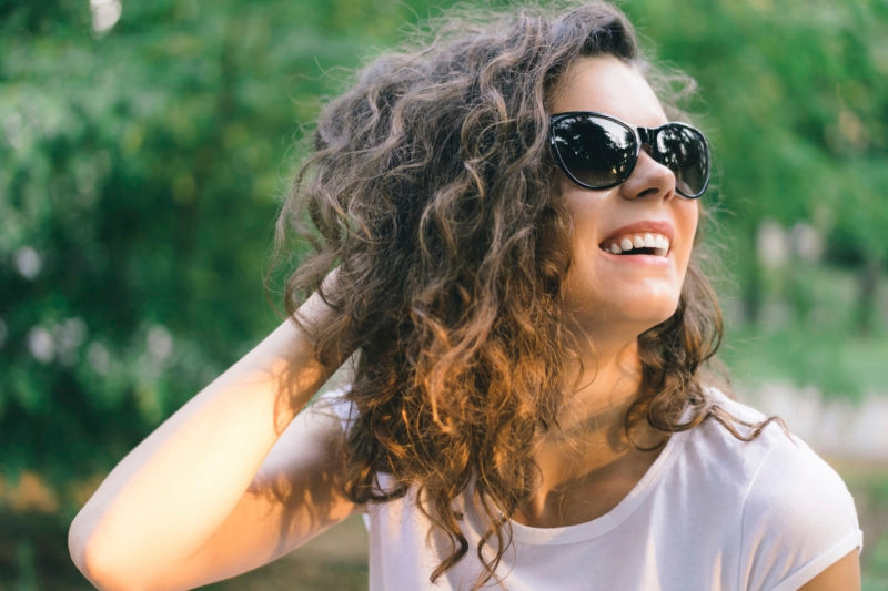 Portrait of a young smiling happy woman in sunglasses at the park on a background of green trees. Girl with curly hair outdoors in the summer.