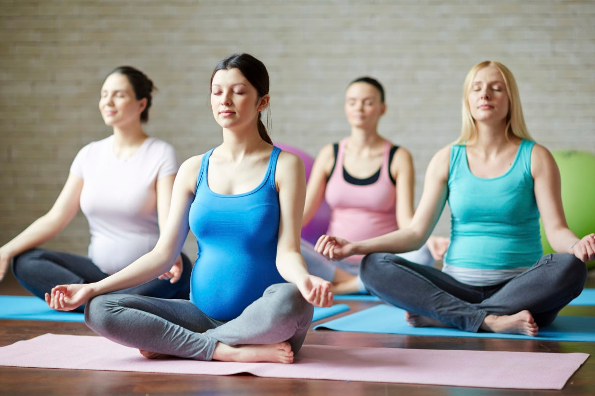 Several pregnant women practicing yoga in gym