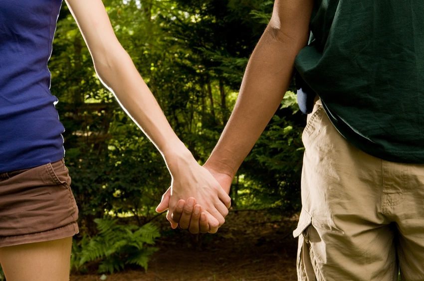 teenage romance – young interracial couple holding hands