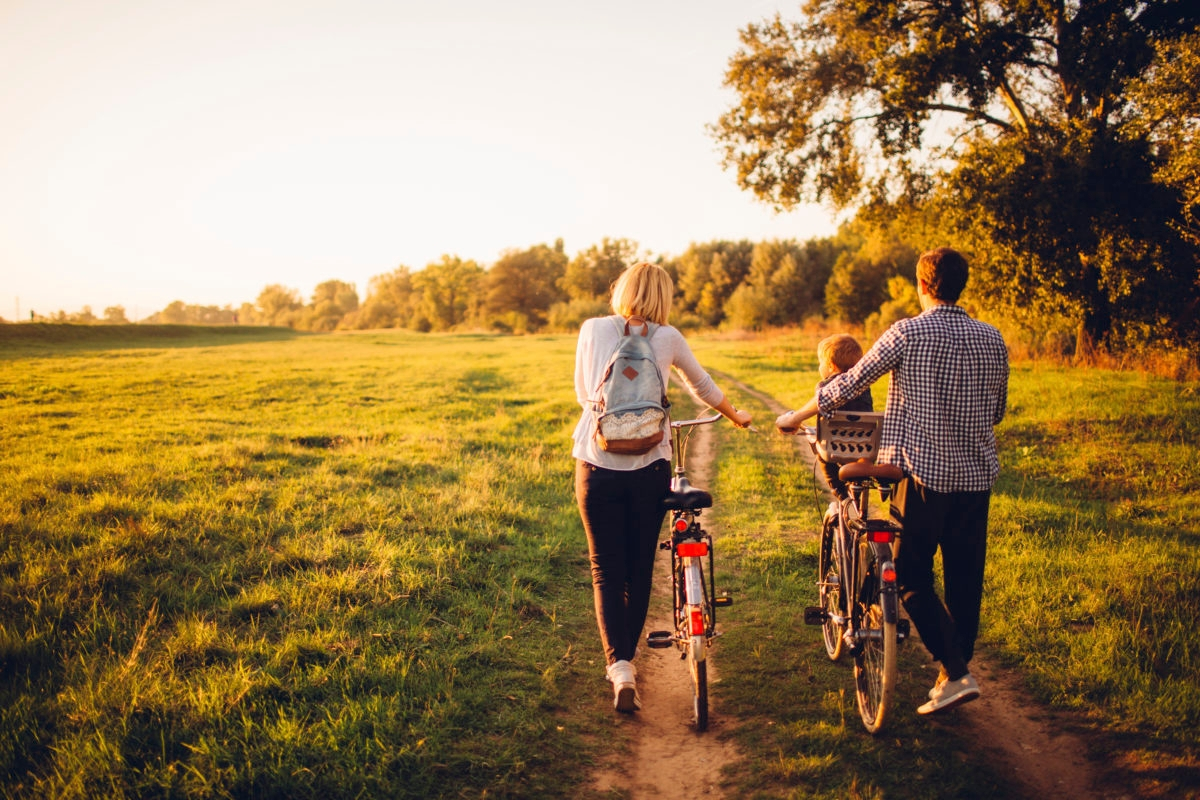 Young family with one child is cycling together outdoors