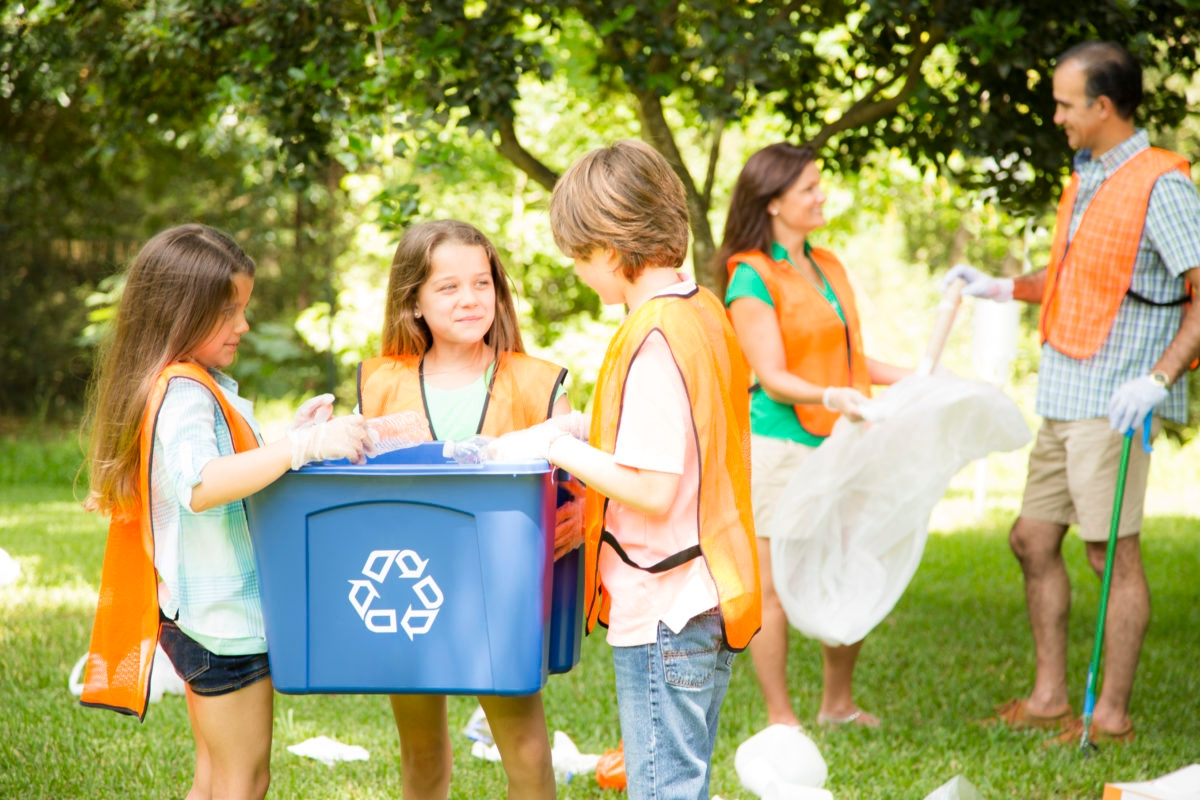 Community volunteers clean up their local park. Family recycles trash. Children are standing in the foreground holding a recycling bin as mother and father pick up garbage in the background and hold garbage bags. Father, mother and three children all wear safety vests. Environmental conservation. Nature.