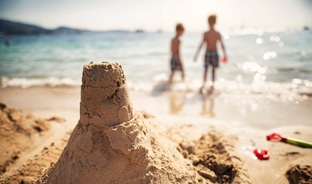 Two little brothers have just built a sandcastle. Sunny summer day.