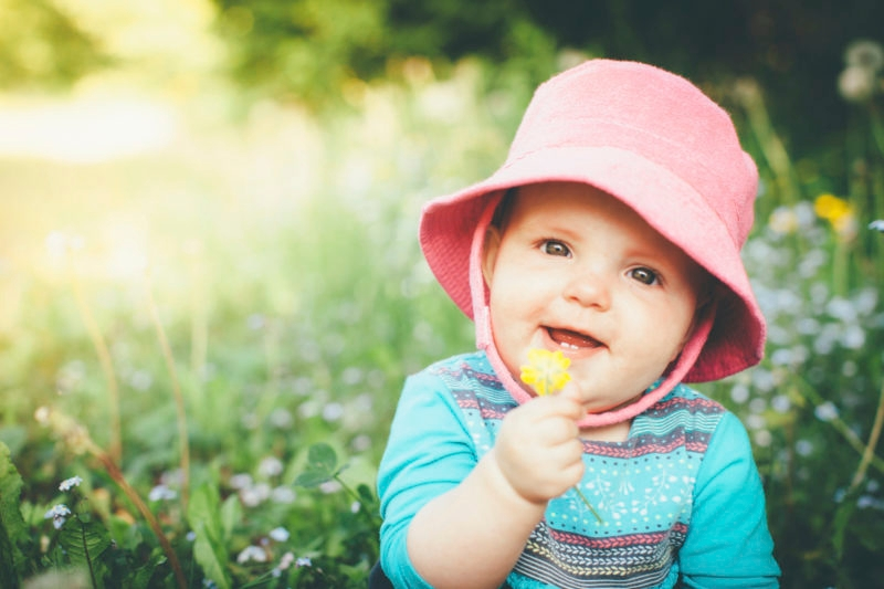 Happy baby girl sitting in a meadow, holding a buttercup flower.