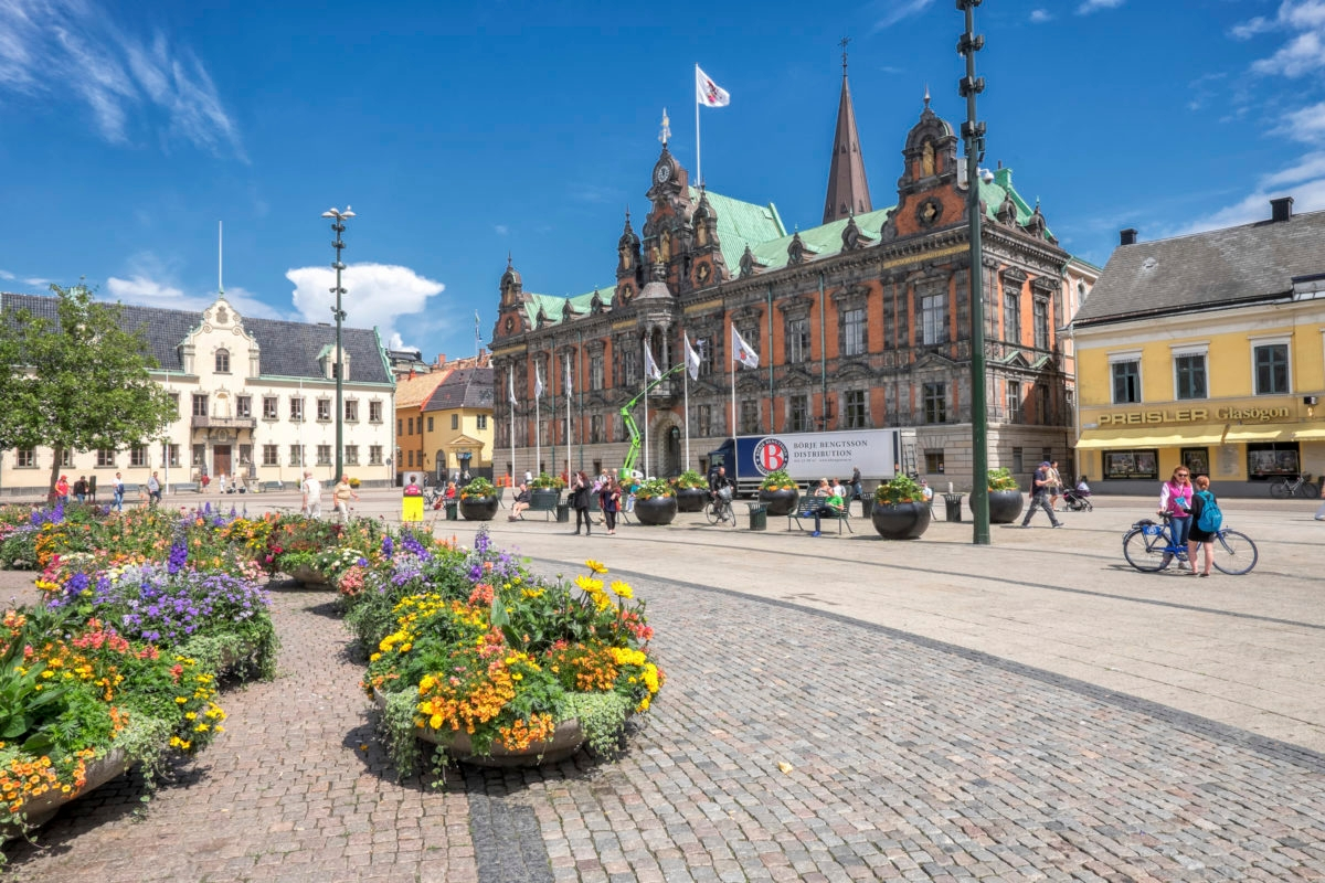 Malmo, Sweden – July 2, 2014: People stroll the big square in front of the old city hall in Malmo on a sunny summer day. The square in Sweden's third largest city dates back to the 16th century and is a popular tourist attraction.