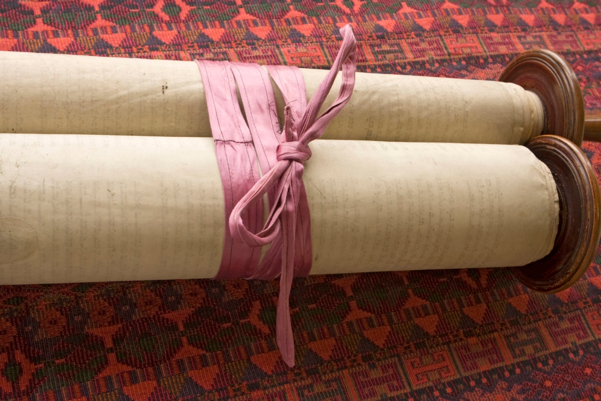 A 150 year-old vintage torah scroll tied with a faded purple ribbon to keep it from unrolling.