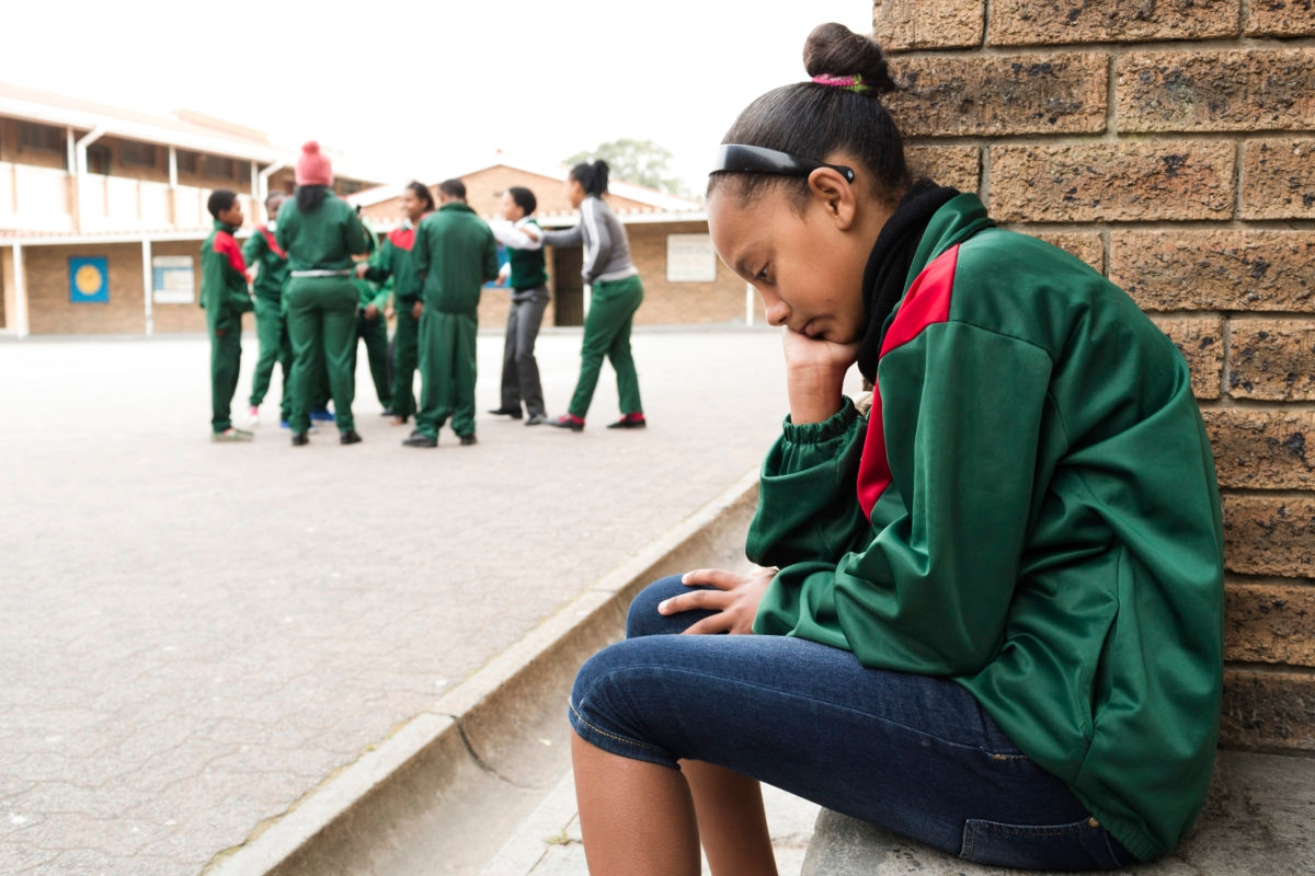 A sad school girl sits on her own as other children play in the background.