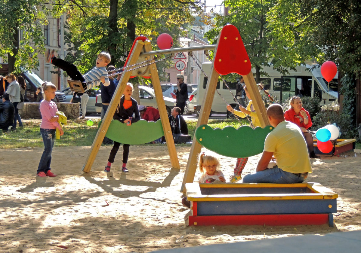 Voronezh, Russia - September 20, 2014: Elementary age and pre-adolescent children have fun on the playground with their parents in a city park