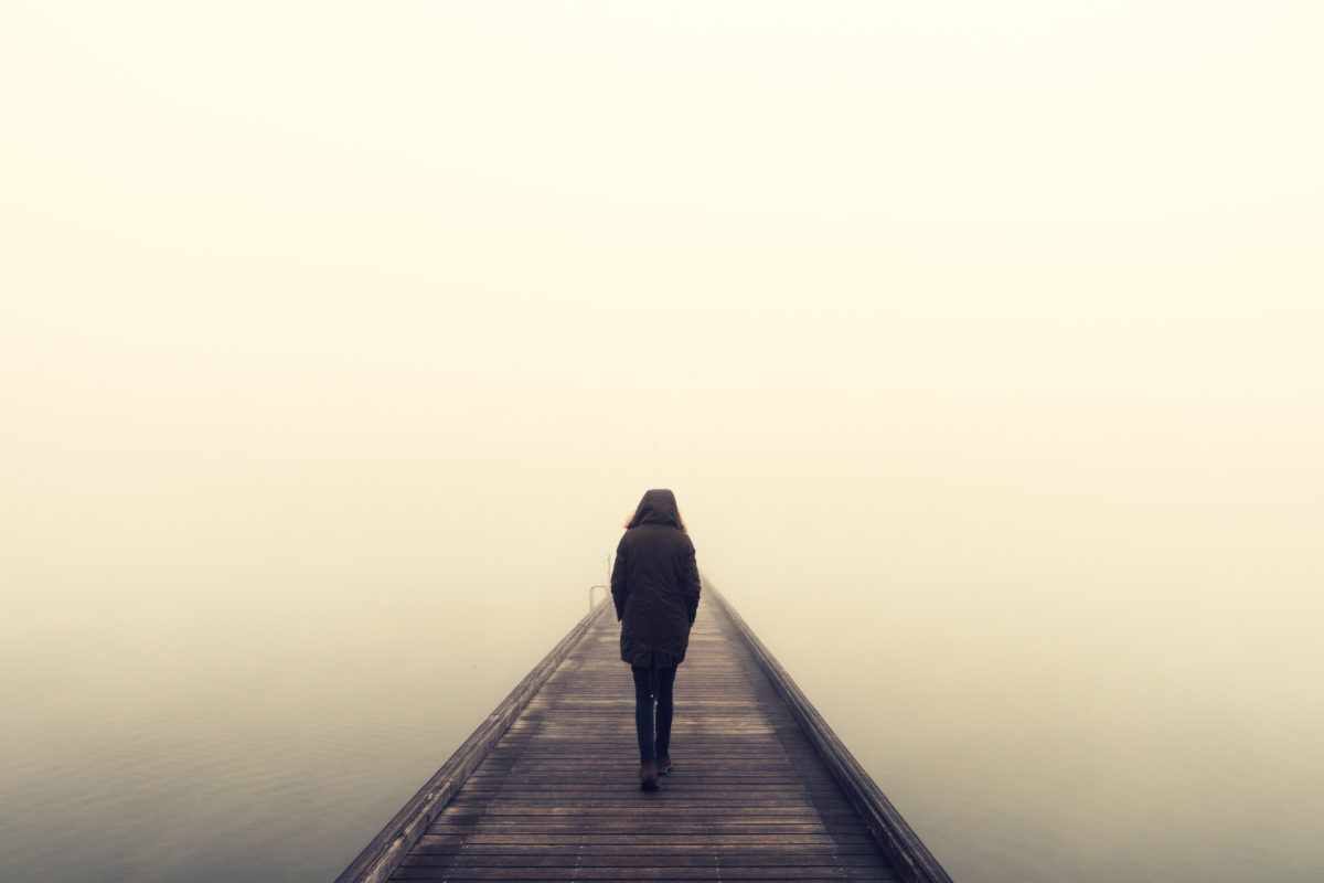 Woman crossing the bridge over lake on a foggy winter day.