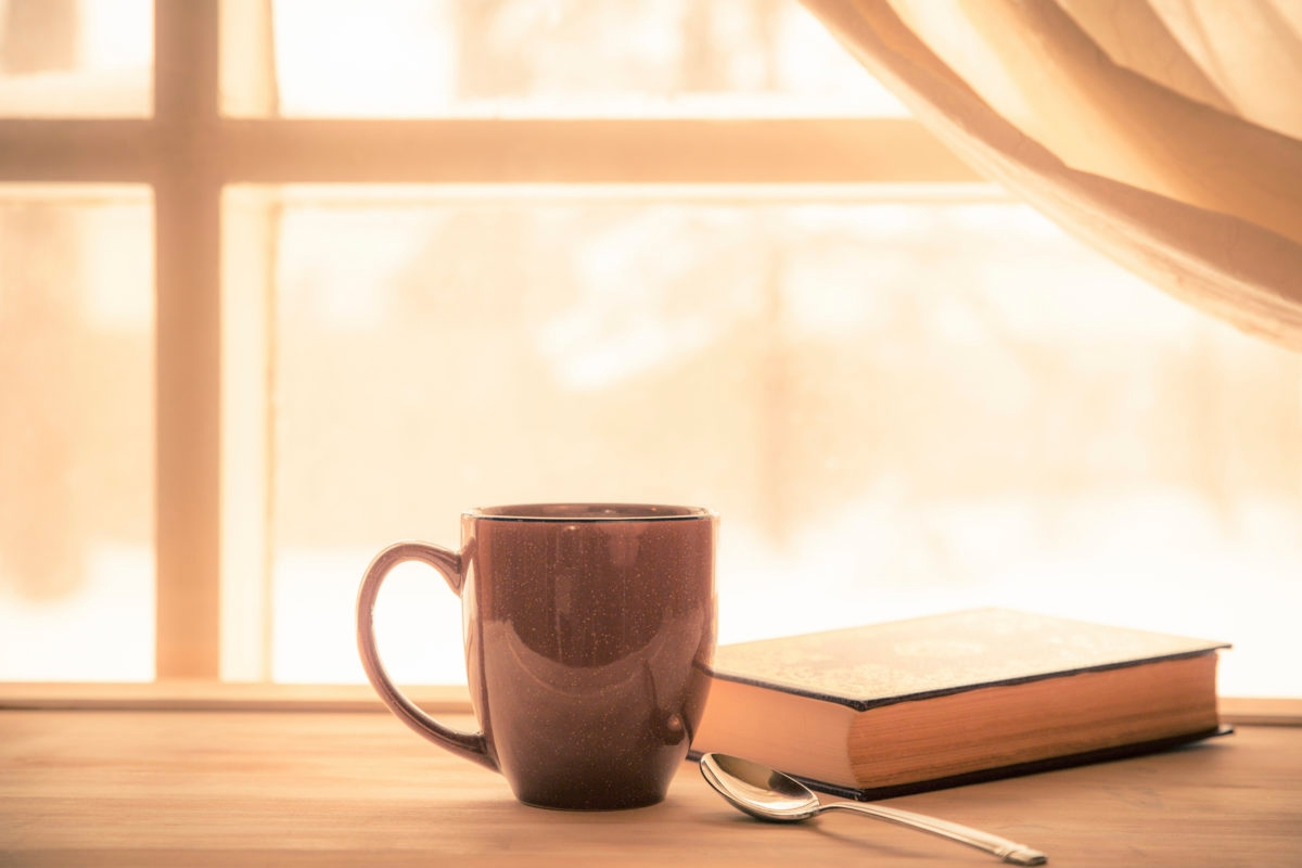 Coffe and Book near window with bright sunny light