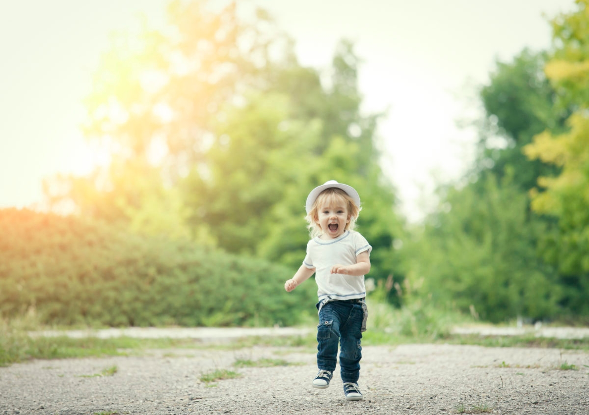 Cute blonde little boy running and having fun outside.