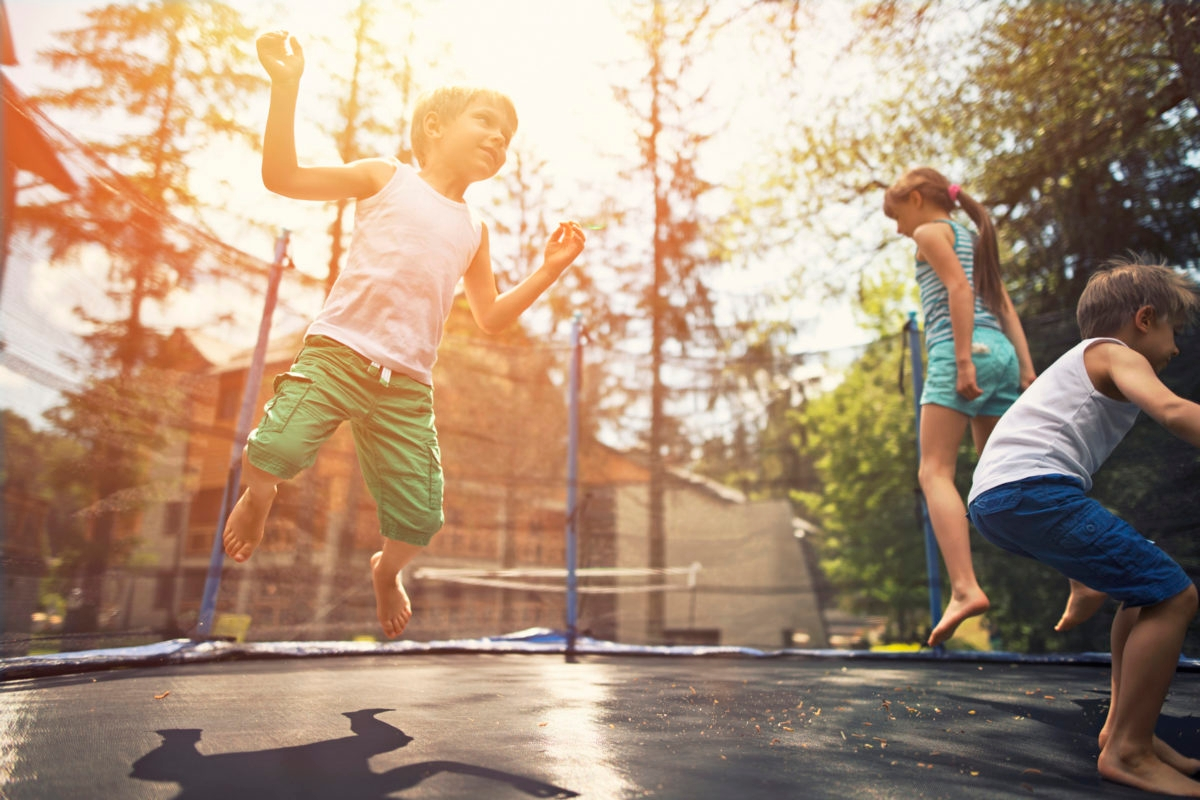 Little boys aged 5 and the girl aged 9 having fun on garden trampoline. Evening sun shining brightly.