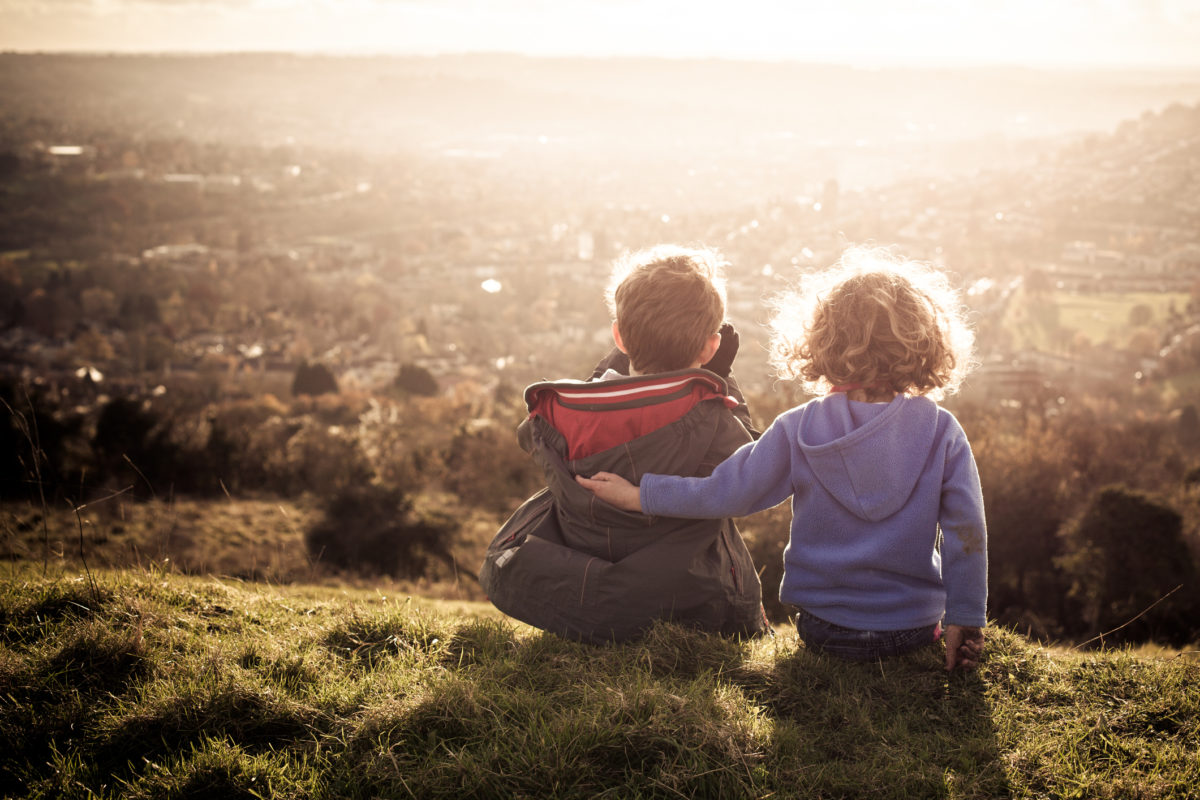Young siblings overlook a city from a hill.