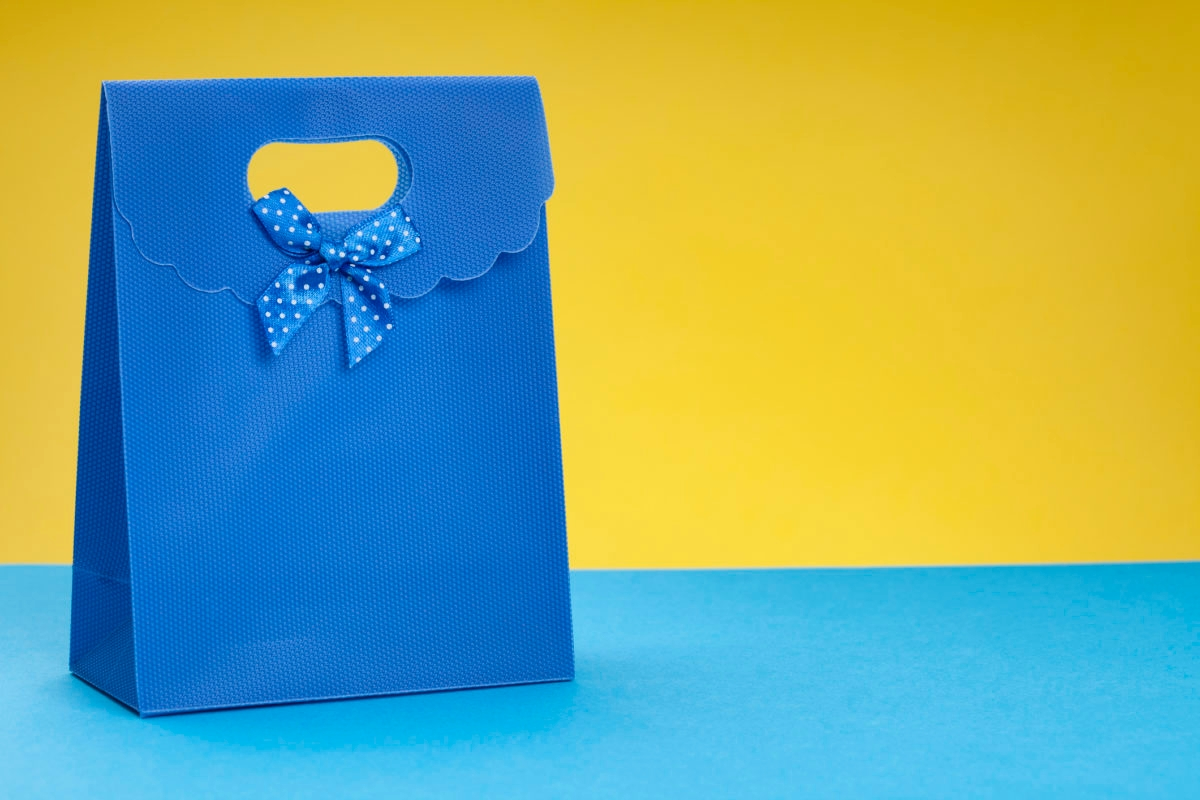 Blue gift bag isolated on yellow