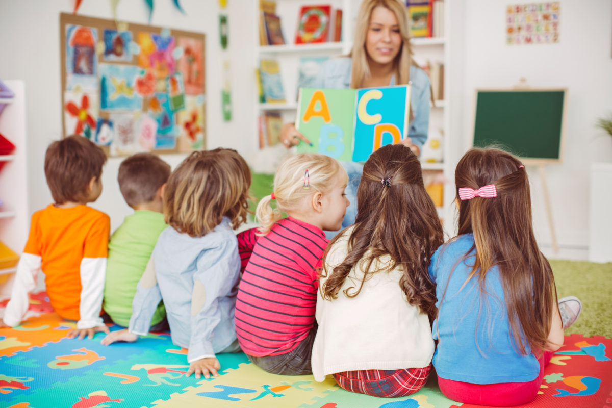 Teacher with a group of preschool children in a nursery. The children are sitting on the floor and listening teacher. Learning letters. In the background we can see a shelf with some, toys, black board and books. View from behind.