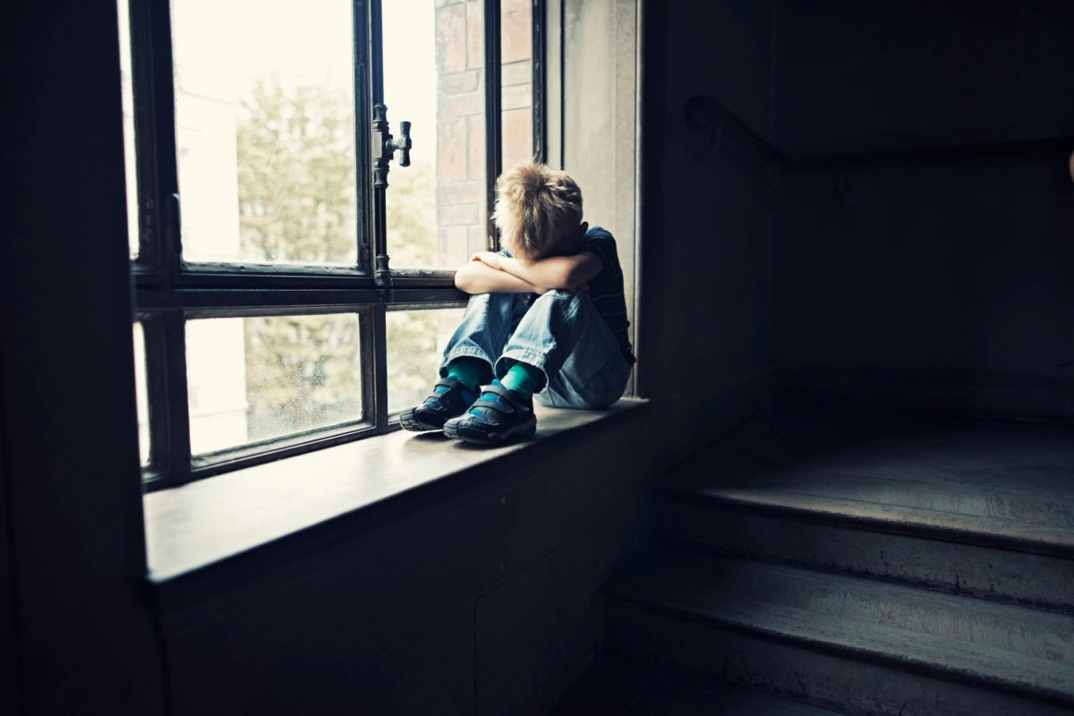 Depressed 6 years old child sitting on window in old staircase. The boy is crying hiding his head in arms.