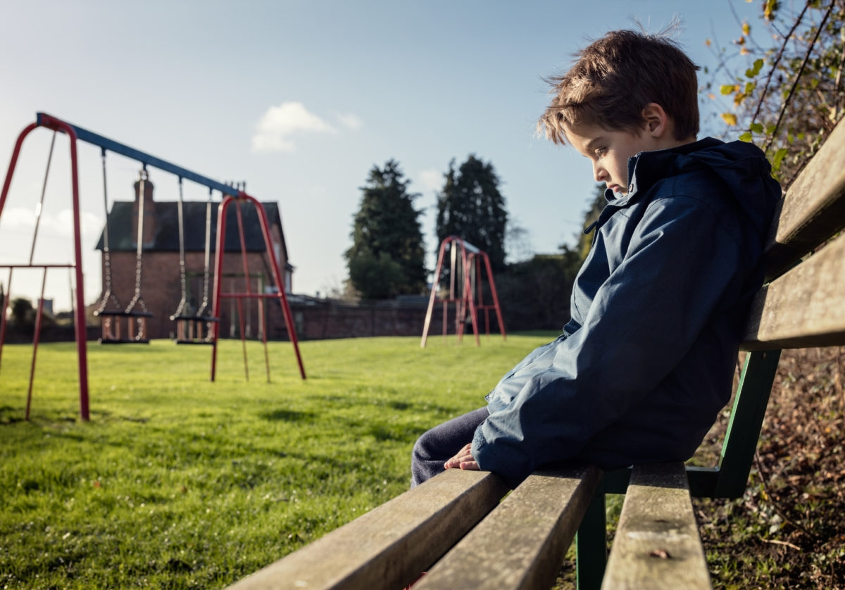 Upset problem child sitting on play park playground bench concept for bullying, depression, child protection or loneliness
