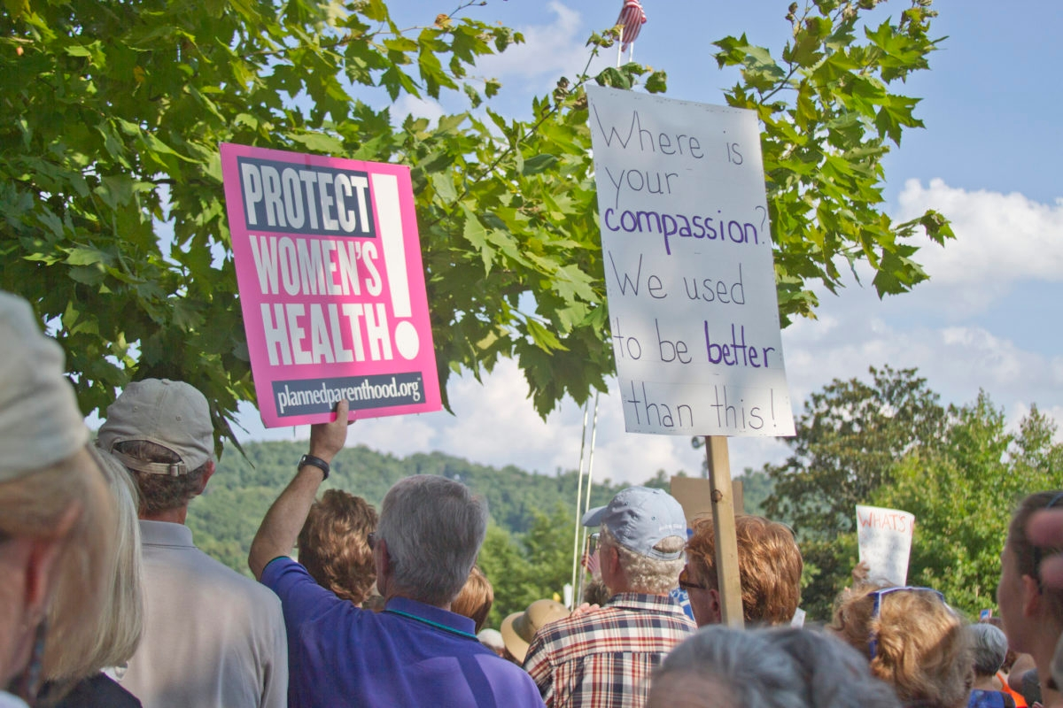 Asheville, North Carolina, USA - August 5, 2013: Protesters hold signs protesting NC state Republican politics at a Moral Monday Rally in Asheville, North Carolina