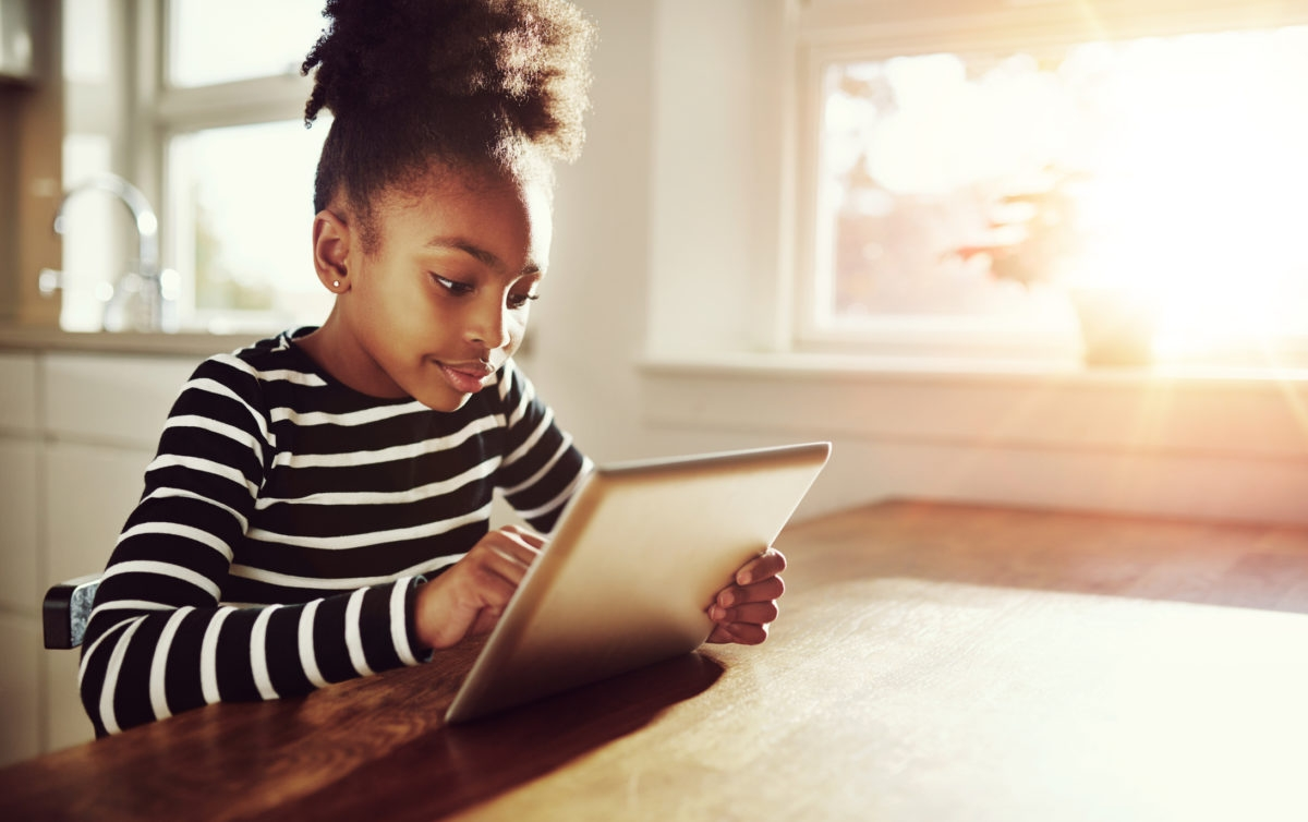 Young black girl with a fun afro hairstyle sitting at a table at home browsing the internet on a tablet computer with bright sun flare through the window alongside her