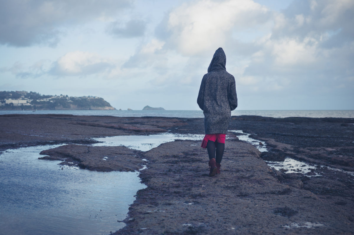 A young woman wearing a hooded coat is walking on a dramatic beach in the winter