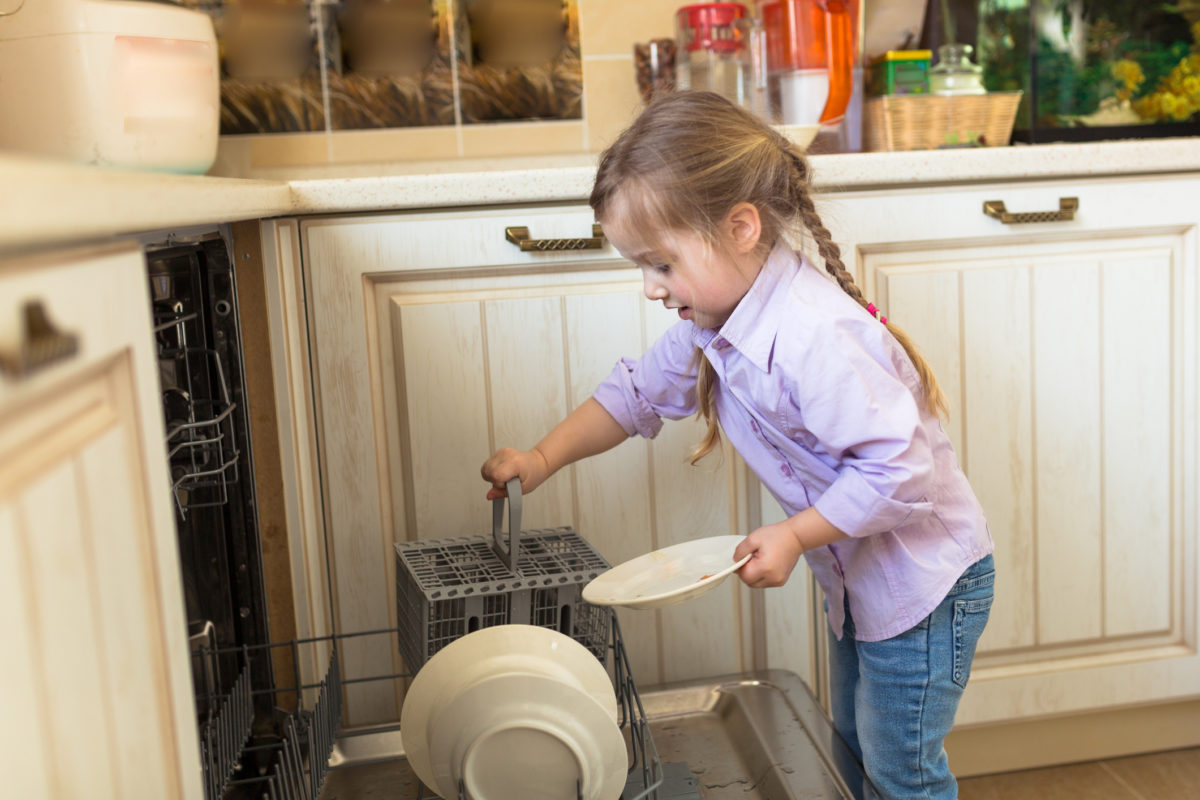 Smiling caucasian girl helping in kitchen taking plates out of dish washing machine, casual lifestyle photo series in real life interior