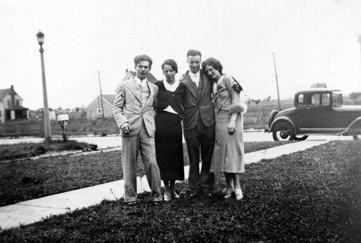 New York, United States - January 01, 1930: Vintage group photograph of an unidentified family standing on the front lawn of their home in New York State, arms on each others' shoulders, with a car and road visible in the background.