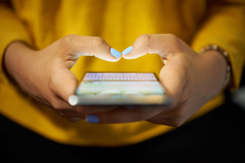 Young woman using cell phone to send text message on social network at night. Closeup of hands with computer laptop in background