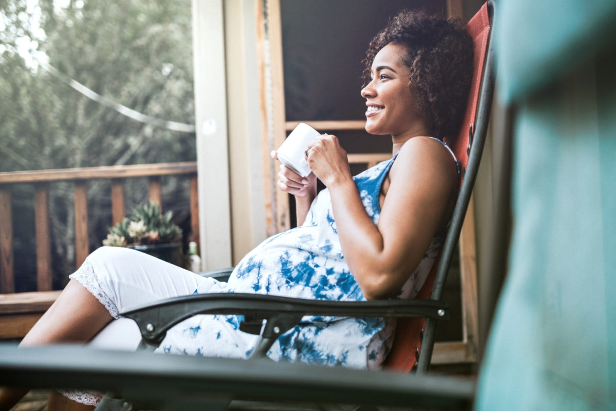 A beautiful African American woman in the 3rd trimester of her pregnancy rests in a recliner on her porch, enjoying a hot drink while anticipating her upcoming child birth. Horizontal image with copy space.