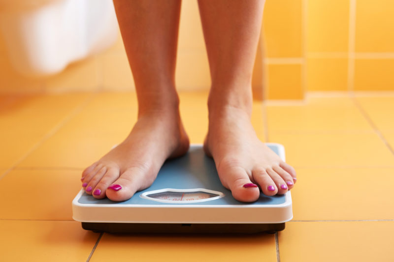 A pair of female feet standing on a bathroom scale