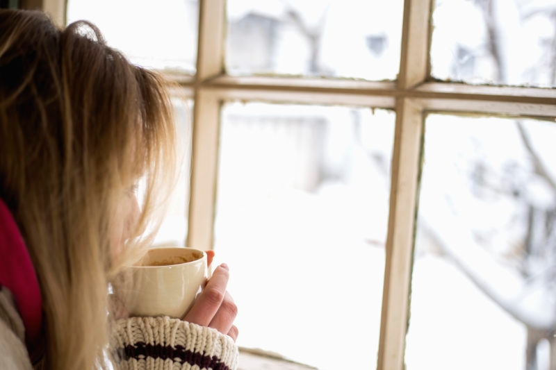 Closeup of woman having a cup of tea or coffee on snowy day. She's sitting in a cafe and looking through window. Wearing knitted cardigan and scarf and enjoying winter in warm and cosy place. Low angle shot.