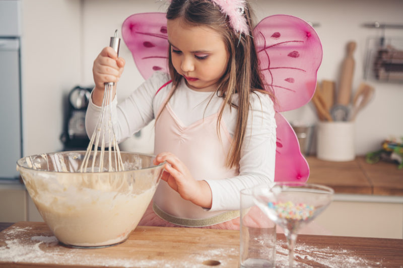 Cute girl mixing batter for muffins. Wearing fairy costume and tiara. Table is messy, with flour all over it.