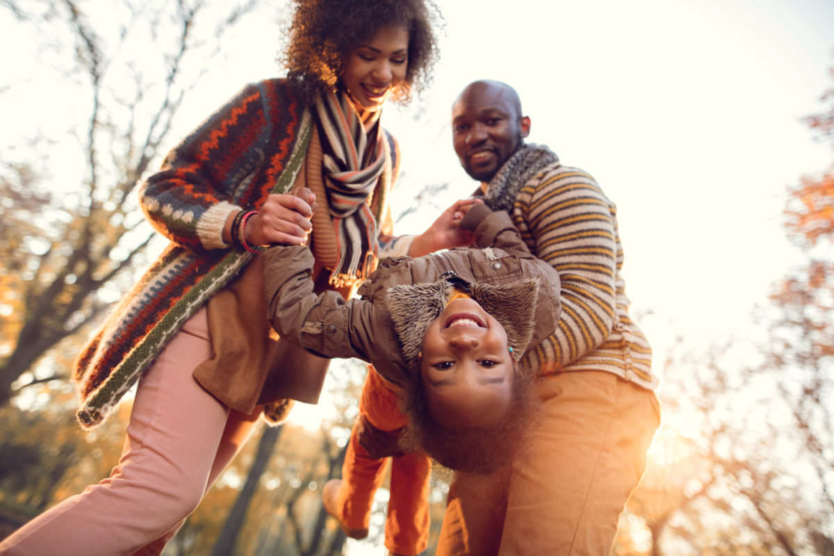 Low angle view of happy African American little girl having fun with her parents in nature during autumn and looking at camera.