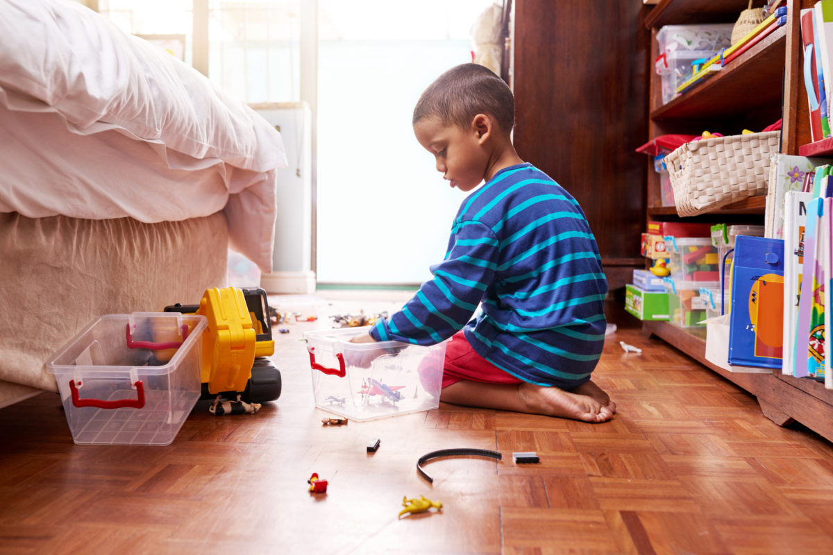Shot of a young boy sitting on the floor with toys in a bedroom