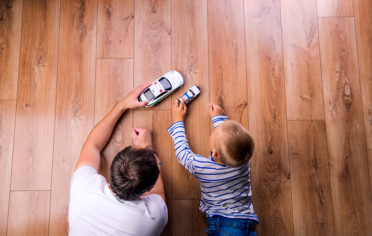 Unrecognizable father with his son playing with cars. Studio shot on wooden background.
