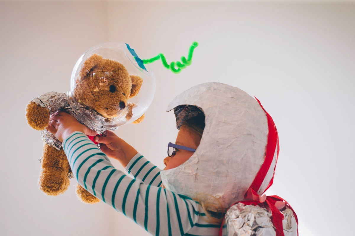 Little girl holding her teddybear, both dressed up as astronauts in homemade helmets, jetpack and spacesuit. The little girl is face to face with her teddy bear as she holds it up and at arms length. Side view of child. She is in a living room at home.