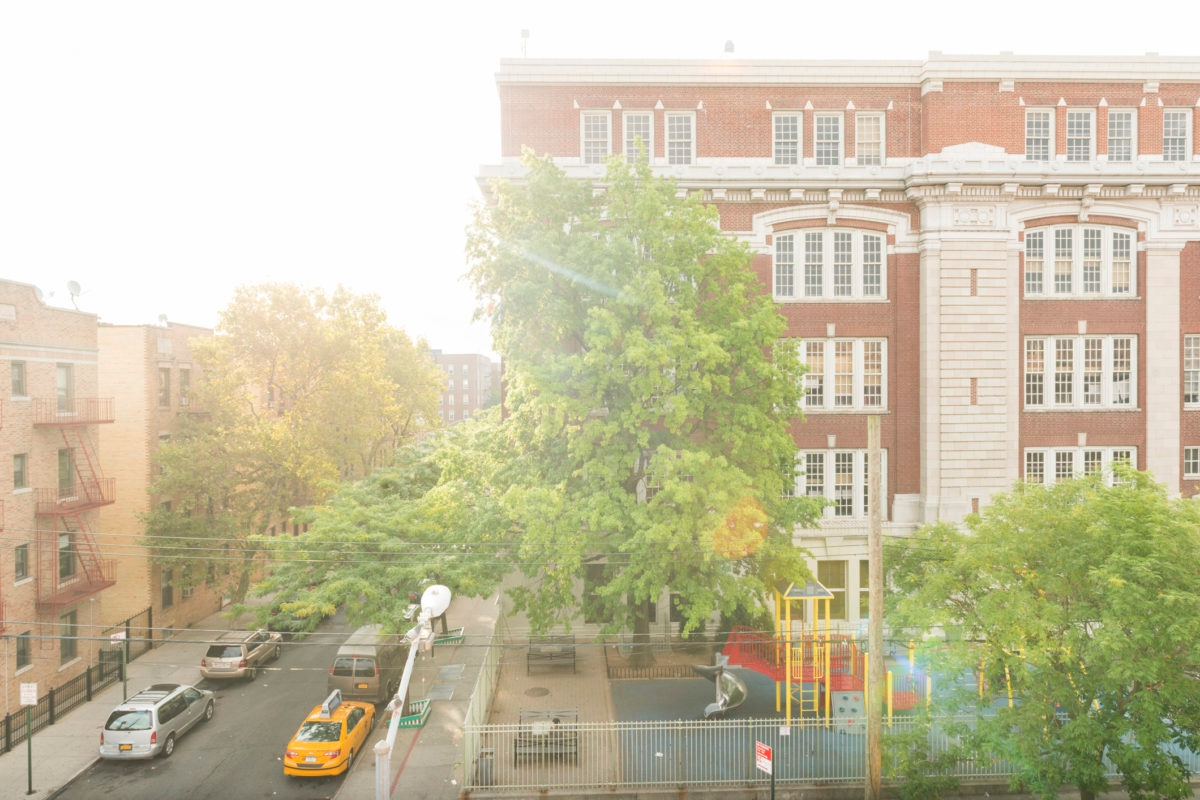 Queens, United States - September 18, 2016: In the Elmhurst neighborhood of this NYC borough an elementary school is housed in a multistory brick building. The morning sun shines brightly over residential buildings and a street lined with parked cars.