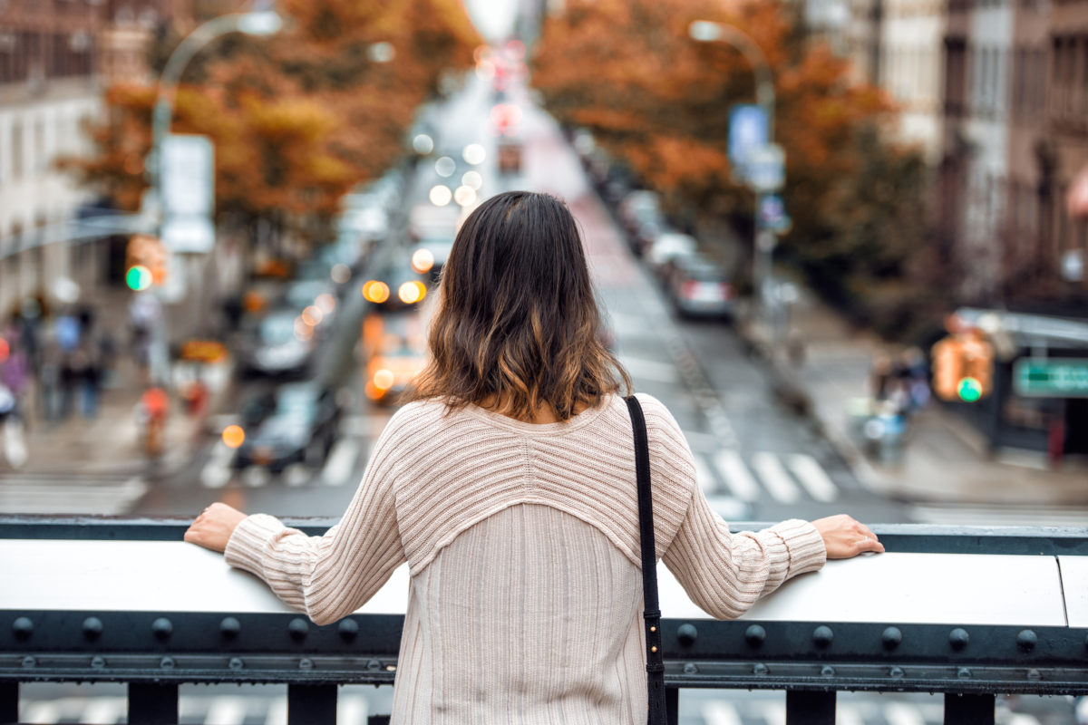 Beautiful woman travel and looking at New York City street with car traffic and yellow trees at autumn time from high point. View from the back.