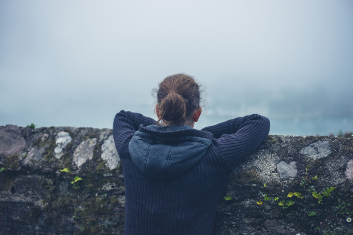 A young woman is resting on a wall outside in the mist