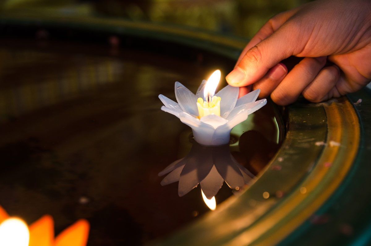 People hand release Lotus flower candle lighting and floating in the water with peaceful and hopeful. faith and belief concept.